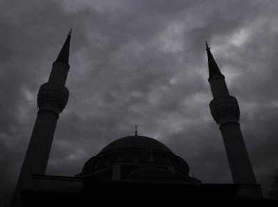 Die Minarette einer Moschee in Berlin ragen in den bewölkten Himmel.