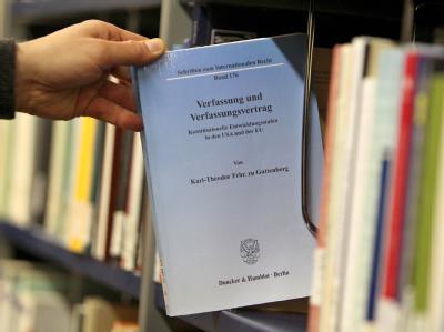 Die Doktorarbeit von zu Guttenberg wird in der Teilbibliothek der Rechts- und Wirtschaftswissenschaftlichen Fakultät der Universität in Bayreuth aus einem Regal genommen.