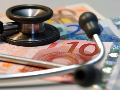 Stethoskop auf Geldscheinen. Mehrere Krankenkassen werden wohl Zusatzbeiträge erheben. (Symbolbild)