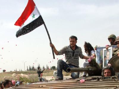 Ein Mann schwenkt auf einem Panzer der Armee die Fahne Syriens. (Archivbild)