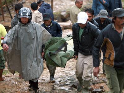 Rettungskräfte mit der Leiche eines der Erdrutsch-Opfer.