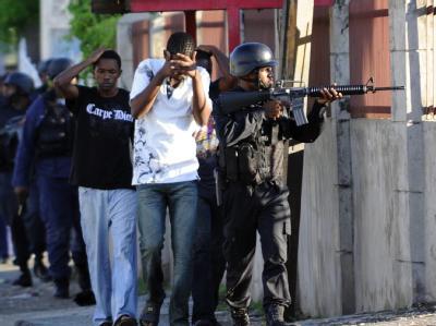 Polizisten führen in Kingston während der Jagd auf
