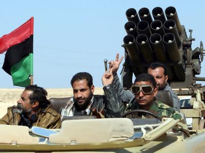 Libysche Rebellen posieren mit Victory-Zeichen für die Kamera.