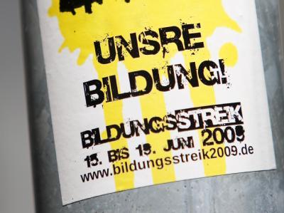 Unter einem Verkehrsschild ist ein Aufkleber mit dem Hinweis auf den Bildungsstreik 2009 angebracht.