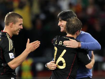 Joachim Löw herzt Philipp Lahm und Lukas Podolski nach dem gewonnenen Viertelfinale zwischen Argentinien and Deutschland in Kapstadt 2010.