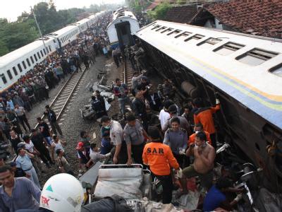 Retter suchen in den Trümmern des in Zentral-Java verunglückten Zugs nach Überlebenden.
