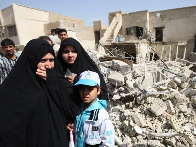 Irakerinnen schauen sich den Tatort eines Anschlags am Wahltag in Bagdad an.
