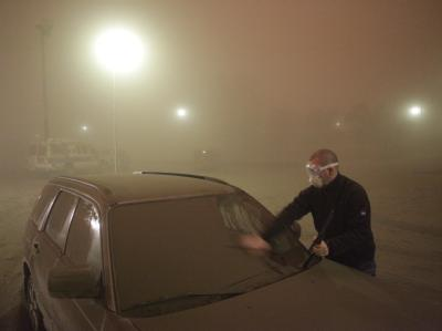 Mit Schutzbrille und Atemmaske reinigt ein Mann im isländischen Kirkjubaejarklaustur sein Auto: Die Bewohner der Insel ächzen unter der Aschewolke des Vulkans Grímsvötn.