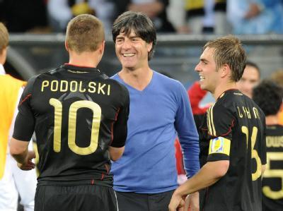 Eine Runde weiter: Bundestrainer Löw freut sich mit Lukas Podolski und Kapitän Philipp Lahm.