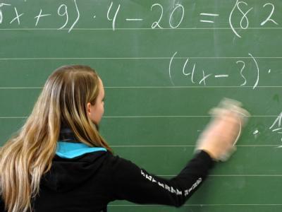Eine Schülerin wischt die Tafel. Der Lehrermangel wird immer dramatischer. (Symbolbild)