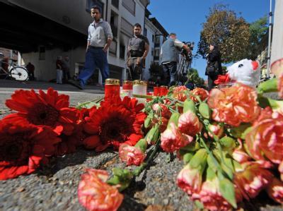 Kerzen und Blumen stehen am 21.09.2010 vor der ausgebrannten Wohnung der Amokläuferin.