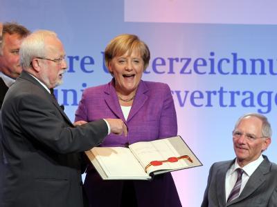 Lachend hält Bundeskanzlerin Angela Merkel (CDU) das historische Schriftstück in den Händen. V.l.: Der ehemalige DDR-Staatssekretär Günther Krause, Lothar de Maiziere, Bundeskanzlerin Merkel und Bundesfinanzminister Schäuble, ehemals Bundesinnenminister.