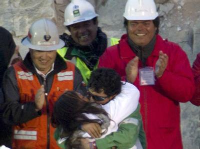 Ein geretteter Bergmann küsst seine Verlobte unter dem Applaus der Rettungskräfte.