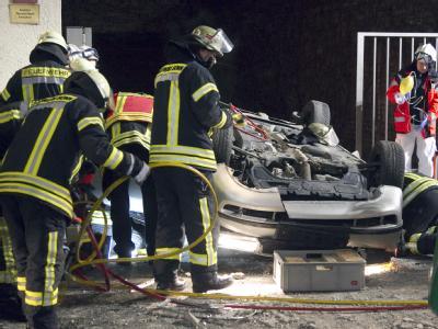 Feuerwehrleute untersuchen das herabgestürzte Auto.