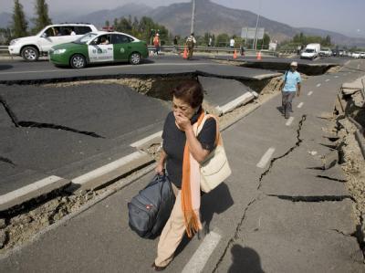 Ein Frau flüchtet auf einer zerstörten Straße aus dem Erdbebengebiet.