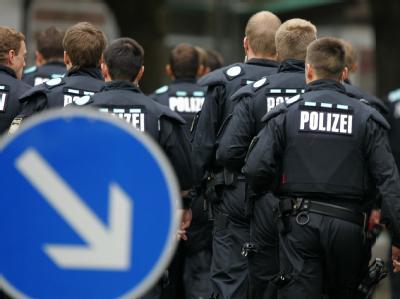Polizisten betreten das Gelände des Carolinum-Gymnasiums in Ansbach (Mittelfranken) .