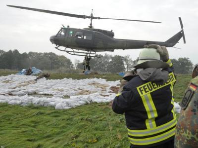 Ein Helikopter der Bundeswehr liefert Sandsäcke für Deiche der Schwarzen Elster bei Mönchenhöfe.