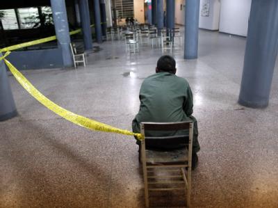 Ein Soldat bewacht ein geschlossenes Wahllokal in Venezuela. Lange Schlangen vor den Urnen sorgten dafür, dass die Lokale am Sonntag verspätet schlossen.