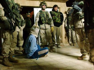 US-Soldaten mit einem verhafteten Iraker. Nach Ansicht der US-Regierung sind die Untersuchungen über Gräueltaten im Irak nicht ihre Angelegenheit.