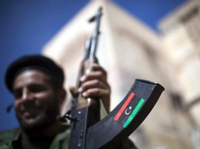 Ein Milizionär des Übergangsrates präsentiert in Sirte seine Waffe (Archivbild: Guillem Valle). Human Rights Watch wirft den Milizionären vor, mehrere Dutzend Gaddafi-Anhänger exekutiert zu haben.