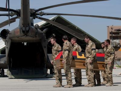 Bundeswehrsoldaten verladen am Ostersonntag 2010 im Feldlager in Kundus die Särge von drei gefallenen Kameraden in einen Helikopter.