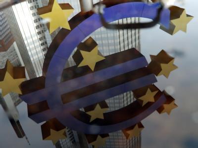 In einer Wasserlache spiegelt sich das Euro-Symbol vor der Europäischen Zentralbank in Frankfurt. Foto: Uwe Zucchi