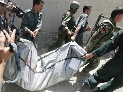 Afghanische Polizisten tragen einen Leichensack weg. Einem Beobachter zufolge hat die Gewalt der Taliban zur Einschüchterung der Wähler beigetragen.
