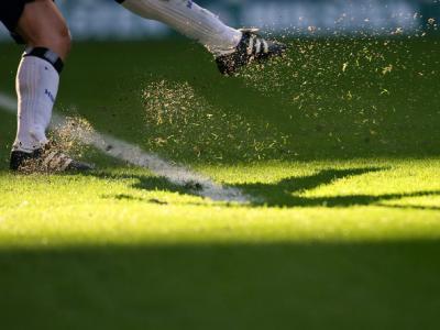 Ein Torwart spielt in einem Fußballspiel den Ball ab.