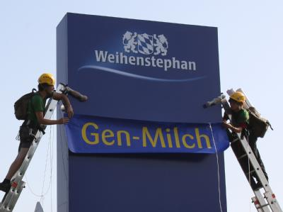 Aktivisten der Umweltschutzorganisation Greenpeace bekleben ein Schild der Molkerei Weihenstephan in oberbayerischen Freising mit der Aufschrift «Gen-Milch» (Archivbild).