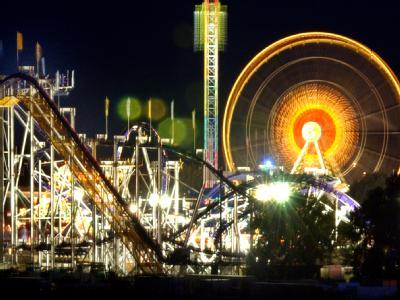 Glühlampenzauber: Im nächtlichen Lichterglanz stehen das Riesenrad und die Achterbahn