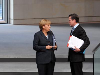 Bundeskanzlerin Angela Merkel (CDU) unterhält sich  im Bundestag mit Bundeswirtschaftsminister Karl Theodor zu Guttenberg (CSU). (Archivbild)