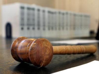 Ein hölzerner Hammer auf der Richterbank eines Gerichts. (Symbolbild)