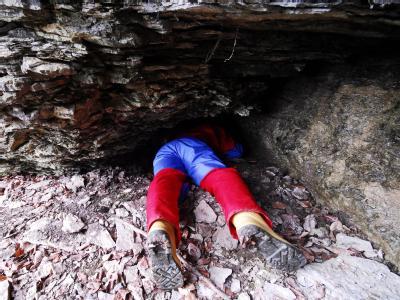 Ein Höhlenforscher kriecht in eine Felsspalte. (Archivbild)