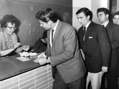 Gastarbeiter aus Italien tauschen am 15.12.1962 auf der Post in Wolfsburg DM gegen Lire (Archiv).