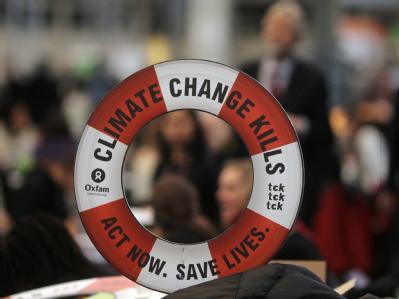 Ein Rettungsring mit aussagekräftiger Aufschrift ist bei der UN-Klimakonferenz im Vordergrund zu sehen.