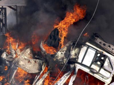 Flammen schlagen aus dem Wrack eines Wagens.
