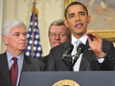 US-Präsident Barack Obama bei einer Pressekonferenz zur Gesundheitsreform. Im Hintergrund die demokratischen Senatoren Christopher Dodd und Max Baucus.