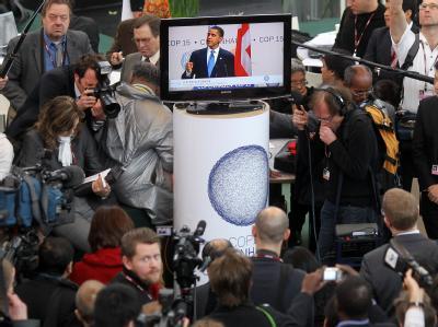 Gipfelteilnehmer und Journalisten schauen die Rede von US-Präsident Barack Obama auf einem Monitor an.