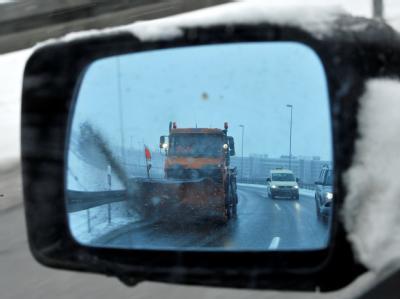 Hilfe kommt: Ein Schneeräumfahrzeug ist auf der Zubringerstraße zum Flughafen München im Rückspiegel eines Autos zu sehen.