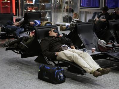 Gestrandete schlafen im Frankfurter Flughafen in einem Wartebereich.