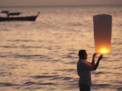 Ein Tourist aus Finnland entzündet am Bangniang Beach eine Laterne in Erinnerung an seinen guten Freund, der bei dem Tsunami 2004 ums Leben kam. Foto: Rungoj Yongrit/Archiv