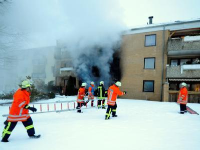 Rettungskräfte bergen Bewohner eines brennenden Mehrfamilienhauses in Bad Bevensen.