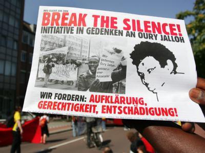 Demonstranten wenden sich mit einem Plakat gegen die ihrer Meinung nach schleppende Aufklärung des Feuertodes von Oury Jalloh. (Archivbild)