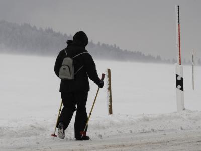 Eine Frau läuft wetterfest gerüstet durch das Schneetreiben. (Bild:dpa)