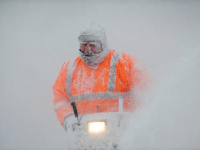 Mit einer Schneefräse räumt ein Mann in Riefensbeek im Harz seine Einfahrt frei.