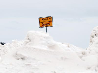 Das Ortsausgangsschild von Gingst (Westrügen) ragt aus einer großen Schneewehe hervor.