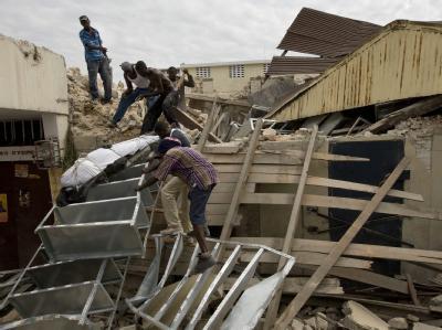 Rettungskräfte bergen einen Toten aus den Trümmern eines Hauses.