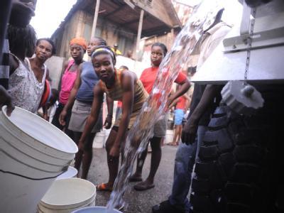 Frauen stehen in Port-au-Prince Schlange, um ihre Eimer mit Wasser zu füllen.