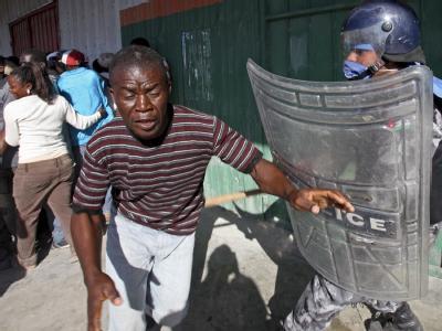 Ein UN-Polizist in Kampfmontur stellt sich einer Gruppe Haitianer in den Weg.
