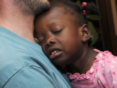 Eine Vierjährige aus Haiti an der Schulter ihres neuen Adoptivvaters.